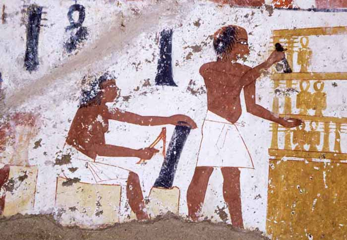 Detail - Worker uses adze to rough out a column of blackwood for a Djed amulet. These objects are associated with Osiris, the Egyptian God of the afterlife and their design is meant to represent the vertebral column.