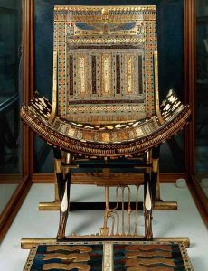 Tutankhamun's Throne Chair -Ceremonial chair made primarily of blackwood, covered with gold leaf and inlaid with ivory and stones. Blackwood inlaid footrest on floor depicts nine traditional enemies of Egypt bound in chains – the enemies are beneath the pharaoh's feet as a sign of subjugation.