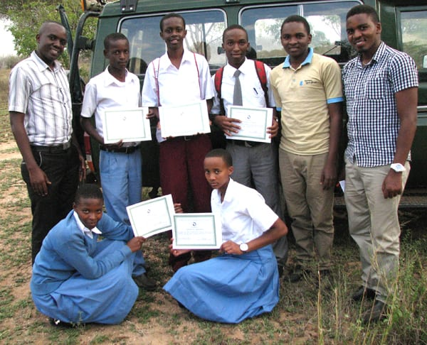 Cyril and Michael (rt) supplied tree seedlings from the ABCP nursery for a Roots and Shoots graduation ceremony. Successful students display their diploma certificates.